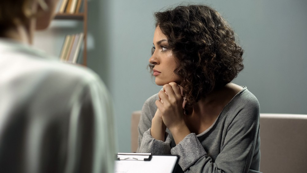 A client with a therapist discussing her trauma and how it may be linked to her depression.