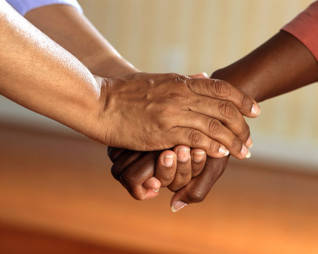 Loved ones holding hands to help one another through addiction.